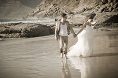 Junge attraktive Paare, die entlang tragendes Weiß des Strandes gehen Stockfoto