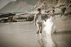 Junge attraktive Paare, die entlang tragendes Weiß des Strandes gehen Stockbilder