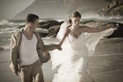 Junge attraktive Paare, die entlang tragendes Weiß des Strandes gehen Stockfotografie