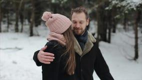 Junge attraktive Paare, die Spaß in einem Winterwald unter starken Schneefällen gehen und haben Mann und Frau im rosa Hutumarmen stock video footage