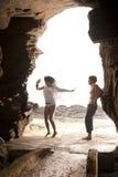 Junge attraktive Paare, die Tanzen durch Felsentorbogen haben Stockfoto