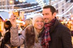 Junge attraktive Paare in einem Weihnachtsmarkt Lizenzfreie Stockbilder