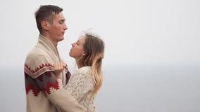 Junge attraktive Paare in gestrickten Strickjacken auf einer Klippe auf Seeufer, dem Necken, dem Umarmen und dem Küssen stock footage