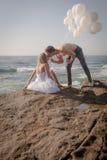 Junge attraktive Paare am Strand auf Felsen mit weißen Ballonen lizenzfreie stockbilder