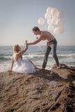 Junge attraktive Paare am Strand auf Felsen mit weißen Ballonen lizenzfreies stockfoto