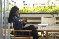 Junge attraktive Schwarzafrikaner Amerikanerin, die draußen am Kaffeestubearbeiten beschäftigt und glücklich sitzt Lizenzfreies Stockbild