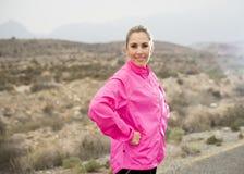 Junge attraktive Sportfrau in der laufenden Jacke, die mit der aufsässigen Haltung aufwirft, kühlen ab Lizenzfreie Stockfotografie