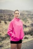 Junge attraktive Sportfrau in der laufenden Jacke, die mit der aufsässigen Haltung aufwirft, kühlen ab Stockbilder