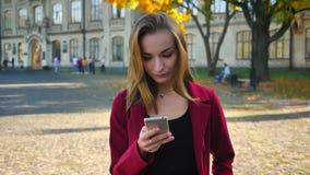 Junge attraktive Studentinmitteilung am Telefon, erhält beleidigt und dann gefallen Messsaging außerhalb stock video footage