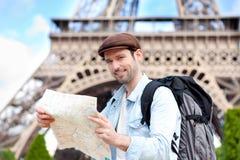 Junge attraktive touristische Lesekarte in Paris Lizenzfreie Stockfotografie