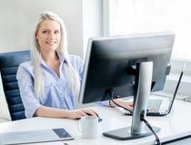 Junge, attraktive und überzeugte Frau, die im Büro arbeitet Stockfotos