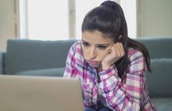 Junge attraktive und gebohrte lateinische Frau auf ihrem 30s, welches zu Hause das Wohnzimmer sitzt auf Couch mit Laptop-Computer lizenzfreie stockfotos
