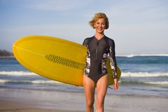 Junge attraktive und glückliche blonde Surferfrau im schönen Strand, der das gelbe Brandungsbrett geht aus Meer heraus Sommer gen lizenzfreie stockfotografie