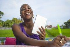 Junge attraktive und glückliche erfolgreiche schwarze afroe-amerikanisch Frau, die draußen mit digitaler Tablettenauflage an grün lizenzfreies stockbild