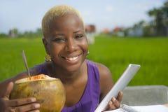 Junge attraktive und glückliche erfolgreiche schwarze afroe-amerikanisch Frau, die mit der digitalen Tablettenauflage draußen tri lizenzfreies stockfoto