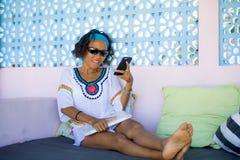 Junge attraktive und glückliche Hippie Asiatin, die den Spaß entspannt unter Verwendung des Internet-Handys an Bettcafé enjoyi dr stockfotografie