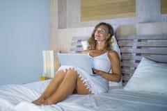 Junge attraktive und schöne glückliche Frau 30s, die zu Hause im Bett unter Verwendung des Internets arbeitet an dem denkenden un Stockbild
