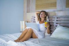 Junge attraktive und schöne glückliche Frau 30s, die zu Hause im Bett unter Verwendung des Internets arbeitet an dem denkenden un Stockbilder