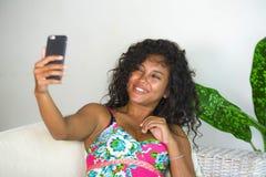 Junge attraktive und schöne glückliche schwarze hispanische Frau, die selfie Porträtphoto mit Handy an der Feiertagswohnung macht stockfotografie