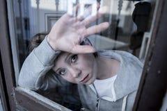 Junge attraktive unglückliche deprimierte einsame Frau, die betontes auf dem Fenster zu Hause sich lehnen schaut Lizenzfreie Stockfotografie