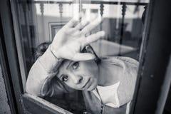 Junge attraktive unglückliche deprimierte einsame Frau, die elendes zu Hause schauen durch das Fenster glaubt Stockfotos