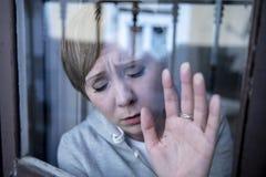 Junge attraktive unglückliche deprimierte einsame Frau, die hoffnungsloses auf dem Fenster zu Hause sich lehnen schaut Stockfotografie