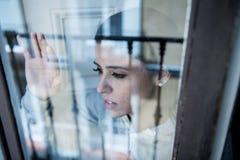 Junge attraktive unglückliche deprimierte einsame Frau, die hoffnungsloses auf dem Fenster zu Hause sich lehnen schaut Lizenzfreies Stockbild