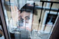 Junge attraktive unglückliche deprimierte einsame Frau, die hoffnungsloses auf dem Fenster zu Hause sich lehnen schaut Lizenzfreie Stockbilder