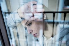 Junge attraktive unglückliche deprimierte einsame Frau, die hoffnungsloses auf dem Fenster zu Hause sich lehnen schaut Stockfotos