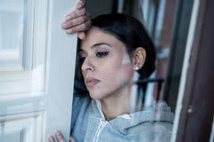 Junge attraktive unglückliche deprimierte einsame Frau, die hoffnungsloses auf dem Fenster zu Hause sich lehnen schaut Lizenzfreie Stockfotos