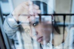 Junge attraktive unglückliche deprimierte einsame Frau, die hoffnungsloses auf dem Fenster zu Hause sich lehnen schaut Lizenzfreie Stockfotografie