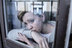 Junge attraktive unglückliche deprimierte einsame Frau, die trauriges zu Hause schauen durch das Fenster schaut Stockbild