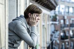 Junge attraktive unglückliche deprimierte einsame Frau, die zu Hause auf dem Balkon traurig schaut Stockbild