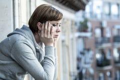 Junge attraktive unglückliche deprimierte einsame Frau, die zu Hause auf dem Balkon traurig schaut Lizenzfreie Stockfotografie