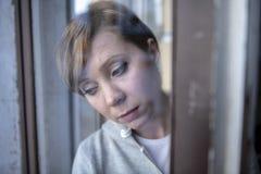 Junge attraktive unglückliche deprimierte einsame Frau, die zu Hause gesorgt und durch das Fenster traurig schaut Lizenzfreies Stockbild