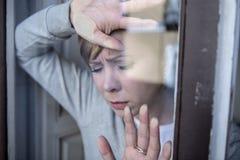 Junge attraktive unglückliche deprimierte einsame Frau, die zu Hause gesorgt und durch das Fenster traurig schaut Lizenzfreie Stockfotos