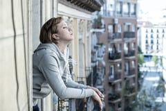 Junge attraktive unglückliche deprimierte einsame Frau, die zu Hause traurig und auf dem Balkon hoffnungslos schaut Stockbild