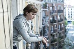 Junge attraktive unglückliche einsame Frau, die zu Hause unter Krise auf dem Balkon leidet Städtische Ansicht Stockbild