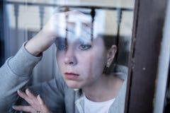 Junge attraktive unglückliche Frau, die unter dem wertlosen Lehnen Krisenanstarrens auf dem Fenster leidet Stockfotografie