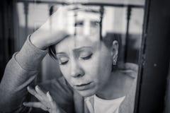 Junge attraktive unglückliche Frau, die unter der Krise schaut das hoffnungslose Lehnen auf dem Fenster leidet Lizenzfreie Stockfotografie