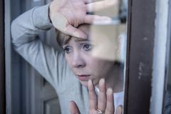 Junge attraktive, unglückliche Frau mit dem Krisenanstarren hoffnungslos durch das Fenster zu Hause Lizenzfreie Stockfotos