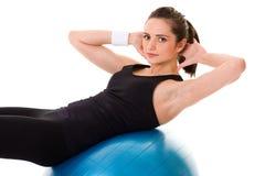 Junge attraktive weibliche Übung unter Verwendung der blauen Kugel Lizenzfreie Stockfotografie