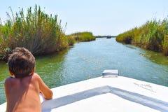 Junge auf dem Boot, bringend im Fluss voran stockfotos