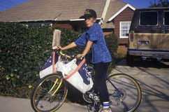 Junge auf dem Fahrrad, das Zeitungen liefert Stockfotografie