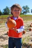 Junge auf dem Kürbisgebiet Stockfotos