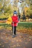 Junge auf dem Roller im Park Lizenzfreie Stockbilder