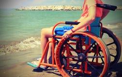 Junge auf dem Rollstuhl durch das Meer mit Weinlese getontem Effekt lizenzfreies stockbild