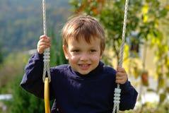 Junge auf dem Schwingen Stockbilder