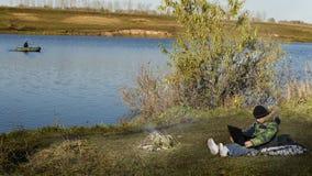 Junge auf dem See mit einem Laptop Lizenzfreies Stockfoto