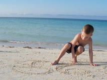Junge auf dem Strand, der im Sand spielt Stockbild